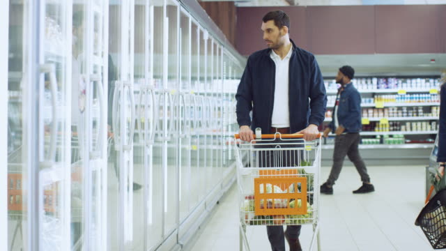 At the Supermarket: Handsome Man Opens Freezer Door and Puts Frozen Vegetables into His Shopping Cart. Customer Browsing Through Frozen Goods Section of the Store.
