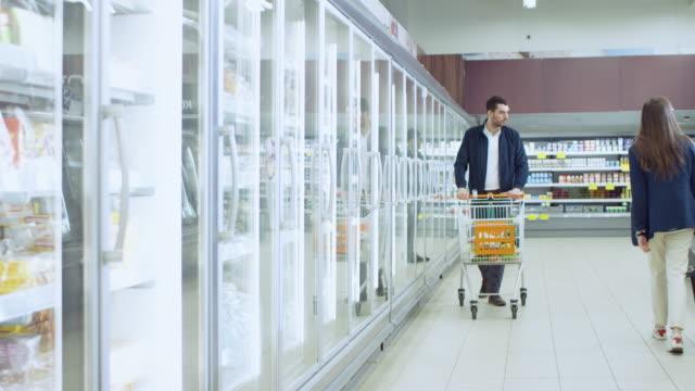 в супермаркете: красивый человек толкает покупки карты и просмотры продуктов в разделе замороженных товаров. человек смотрит в стеклянный  - супермаркет стоковые видео и кадры b-roll
