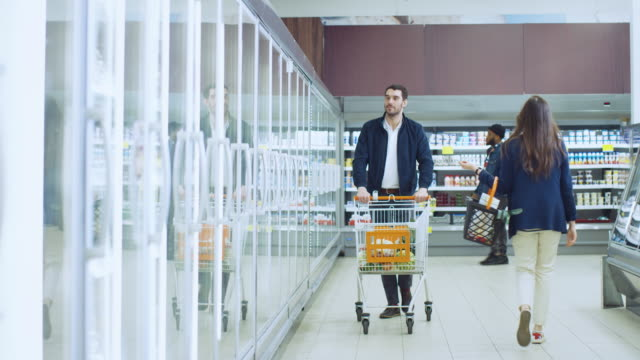 at the supermarket: handsome man pushes shopping card and browses for products in the frozen goods section. man looks into glass door fridge, choosing dairy products. other customer shopping. - замороженные продукты стоковые видео и кадры b-roll