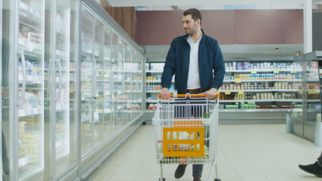 at the supermarket: handsome man pushes shopping card and browses for products in the frozen goods section. other customer in the background. - замороженные продукты стоковые видео и кадры b-roll