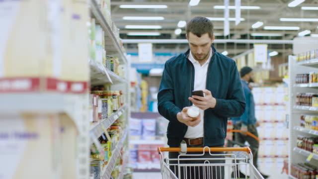 vídeos y material grabado en eventos de stock de en el supermercado: hombre guapo usa smartphone y navega a través de la plataforma de mercancías conservadas. él está de pie con el carrito en la sección de enlatados. - eventos de etiqueta