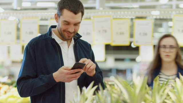 vídeos de stock e filmes b-roll de at the supermarket: handsome man uses smartphone, browses through internet and smiles charmingly while standing near fresh produce section where he chooses organic fruits. - online shopping