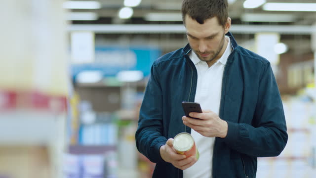 vídeos de stock e filmes b-roll de at the supermarket: handsome man uses smartphone to check nutritional value of the canned goods and buy it. he's standing with shopping cart in canned goods section. - online shopping