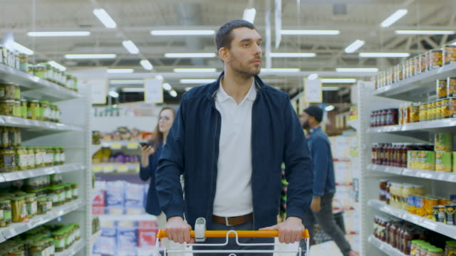at the supermarket: handsome man with shopping cart walks through canned goods section, browsing. big store with lots of aisles. - borsa della spesa video stock e b–roll