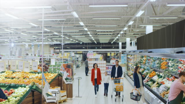 At the Supermarket: Happy Family of Three, Holding Hands, Walks Through Fresh Produce Section of the Store. Father, Mother and Daughter Having Fun Time Shopping. Elevated, High Angle Panoramic Shot.
