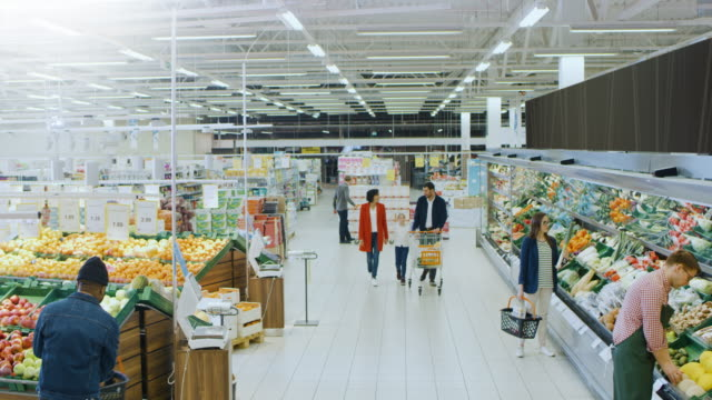 at the supermarket: happy family of three, holding hands, walks through fresh produce section of the store. father, mother and daughter having fun time shopping. high angle panoramic shot of the store. - happy holidays filmów i materiałów b-roll