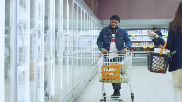At the Supermarket: Happy Stylish Guy Pushes Shopping Cart and Chooses Frozen Vegetables in the Frozen Goods Section of the Store. Big Mall with Glass Door Fridge. At the Supermarket: Happy Stylish Guy Pushes Shopping Cart and Chooses Frozen Vegetables in the Frozen Goods Section of the Store. Big Mall with Glass Door Fridge. Shot on RED EPIC-W 8K Helium Cinema Camera. freezer stock videos & royalty-free footage
