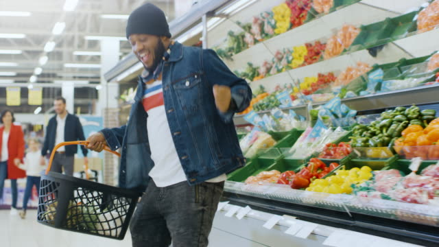 at the supermarket: happy stylish guy with shopping basket dances through fresh produce section of the store. big bright shopping mall with customers choosing goods and products. - świętowanie filmów i materiałów b-roll