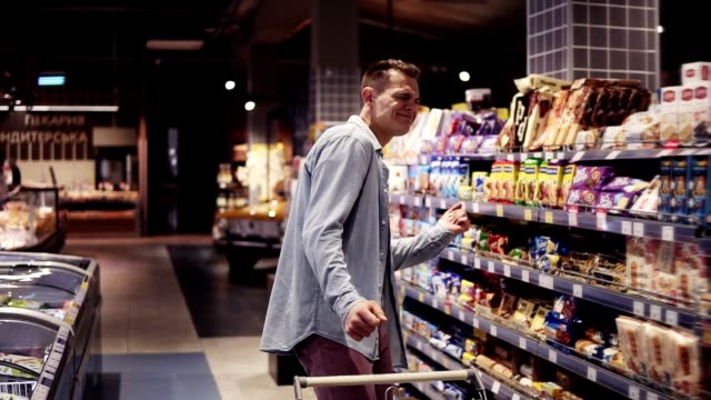 At the supermarket: Happy stylish man with shopping trolley in big shopping mall walking by the shelves with goods and suddenly starts dancing. Positive dances in an empty food store video
