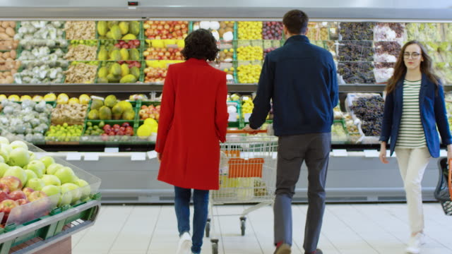 At the Supermarket: Happy Young Couple Chooses Organic Fruits and Berries in the Fresh Produce Section of the Store. Boyfriend Pushes Shopping Cart while Girlfriend Picks up Fruits. At the Supermarket: Happy Young Couple Chooses Organic Fruits and Berries in the Fresh Produce Section of the Store. Boyfriend Pushes Shopping Cart while Girlfriend Picks up Fruits. Shot on RED EPIC-W 8K Helium Cinema Camera. woman pushing cart stock videos & royalty-free footage