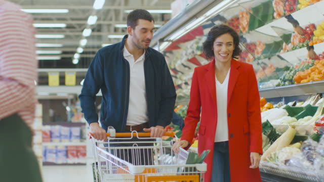At the Supermarket: Happy Young Couple Chooses Organic Vegetables in the Fresh Produce Section of the Store. Boyfriend Pushes Shopping Cart while Girlfriend Picks up Groceries.