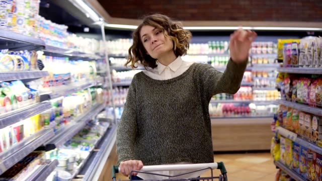 At the supermarket happy young woman dances through goods and dairy products on the shelves. Whirling, having fun, positive. Pushing shopping cart. Front view video