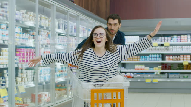 at the supermarket: man pushes shopping cart with woman sitting in it, happy couple has fun while racing on a trolley through the store. slow motion. - happy holidays filmów i materiałów b-roll