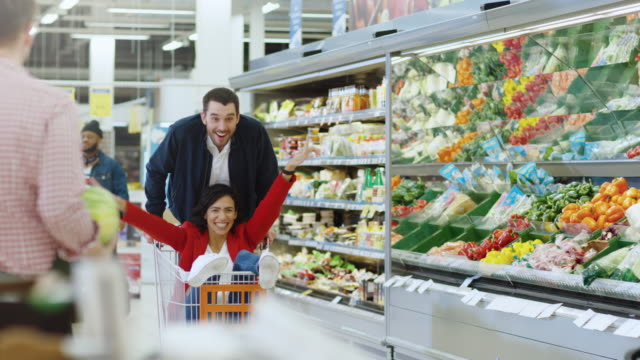 At the Supermarket: Man Pushes Shopping Cart with Woman Sitting in it. Happy Couple Has Fun while Racing on a Trolley through the Fresh Produce Section. At the Supermarket: Man Pushes Shopping Cart with Woman Sitting in it. Happy Couple Has Fun while Racing on a Trolley through the Fresh Produce Section. Shot on RED EPIC-W 8K Helium Cinema Camera. woman pushing cart stock videos & royalty-free footage