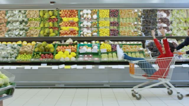 At the Supermarket: Man Pushes Shopping Cart with Woman Sitting in it, Happy Couple Has Fun Racing in a Trolley through the Fresh Produce Section of the Store. Slow Motion Side View Footage. At the Supermarket: Man Pushes Shopping Cart with Woman Sitting in it, Happy Couple Has Fun Racing in a Trolley through the Fresh Produce Section of the Store. Slow Motion Side View Footage. Shot on RED EPIC-W 8K Helium Cinema Camera. woman pushing cart stock videos & royalty-free footage