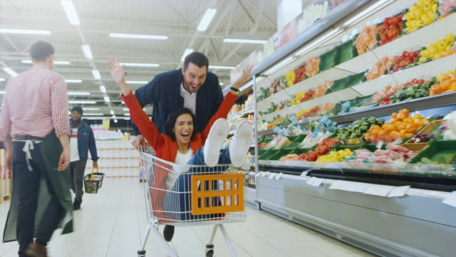 At the Supermarket: Man Pushes Shopping Cart with Woman Sitting in it, Happy Couple Has Fun Racing in a Trolley through the Fresh Produce Section of the Store. At the Supermarket: Man Pushes Shopping Cart with Woman Sitting in it, Happy Couple Has Fun Racing in a Trolley through the Fresh Produce Section of the Store. Shot on RED EPIC-W 8K Helium Cinema Camera. woman pushing cart stock videos & royalty-free footage