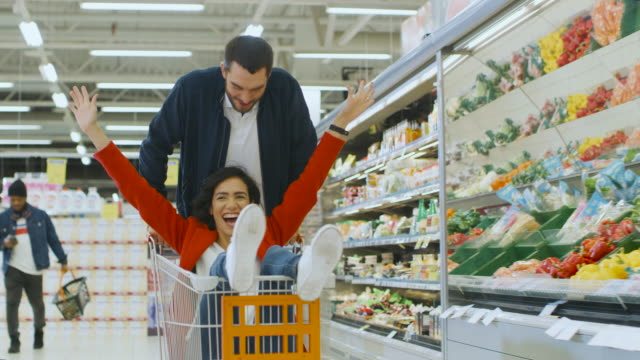 at the supermarket: man pushes shopping cart with woman sitting in it, happy couple has fun racing in a trolley through the fresh produce section of the store. people walking by. - свобода стоковые видео и кадры b-roll