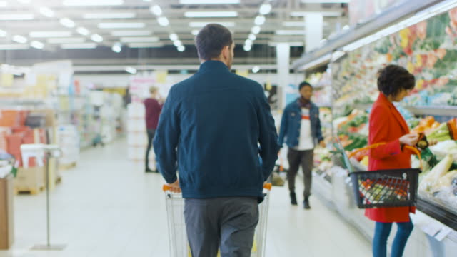 at the supermarket: man pushing shopping cart through fresh produce section of the store. store with many customers shopping. following back view shot. - borsa della spesa video stock e b–roll