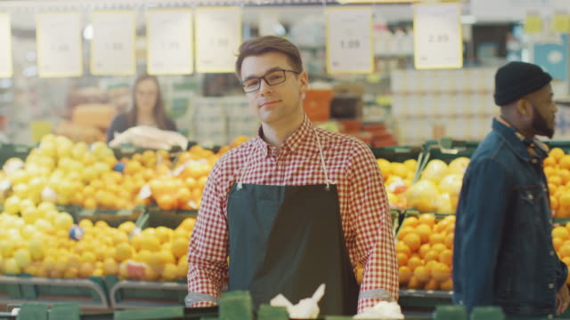 vídeos de stock e filmes b-roll de at the supermarket: portrait of the smiling stock clerk wearing apron, arranging organic fruits and vegetables. friendly, efficient worker at the farmer's market section of the store - prateleira compras