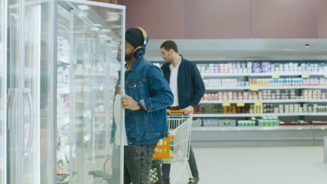 At the Supermarket: Stylish African American Guy with Shopping Basket Chooses Products in the Frozen Goods Section of the Store. He Opens Big Glass Door Fridge. Slow Motion. At the Supermarket: Stylish African American Guy with Shopping Basket Chooses Products in the Frozen Goods Section of the Store. He Opens Big Glass Door Fridge. Slow Motion. Shot on RED EPIC-W 8K Helium Cinema Camera. freezer stock videos & royalty-free footage