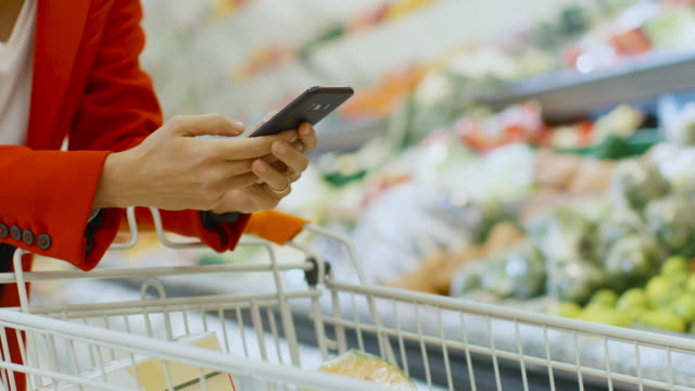 vídeos de stock e filmes b-roll de at the supermarket: woman uses smartphone, leans on the shopping cart. in the big mall woman browsing in internet on her mobile phone. focus on hands holding mobile phone. - online shopping