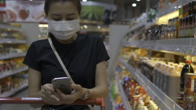 At the Supermarket: Woman Uses Smartphone, Leans on the Shopping Cart