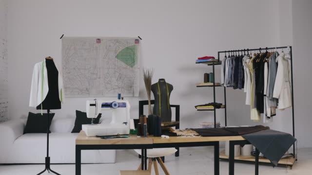 atelier. mode-design-studio. ein stilvolles studio zum nähen von kleidung, die es nähmaschine, spulenfäden, verschiedene nähartikel und stoffe liegen drängen, schaufensterpuppen stehen und skizzen an die wand gepinnt, kleidung auf kleiderbügeln und a - kurzwaren stock-videos und b-roll-filmmaterial
