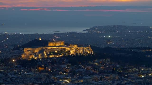 vídeos de stock, filmes e b-roll de atenas, grécia. panning disparado da construção do parthenon e do herodium no monte do acropolis na hora azul - atenas grécia