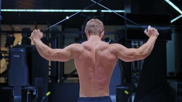 vidéos et rushes de athlète, un bodybuilder, étire les harnais derrière la tête sur le simulateur, entraîne le latissimus dorsi. muscles du dos gonflés en relief. vue de l'arrière. 4k, prores - body building