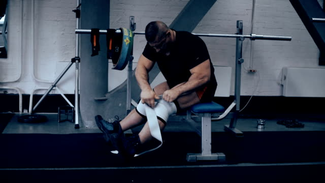 athlete athletic relieve knee bandages after the competition sitting on a bench video