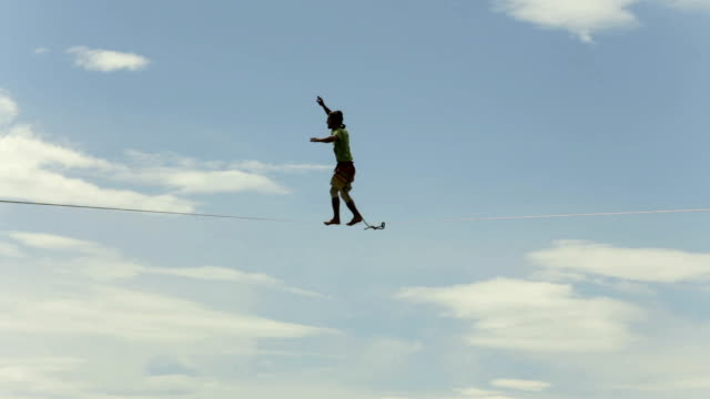 Athlete balances along highline stretched above creek, old town video