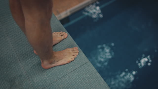 idrotts utövare dykning från plattform till blå pool - på gränsen bildbanksvideor och videomaterial från bakom kulisserna
