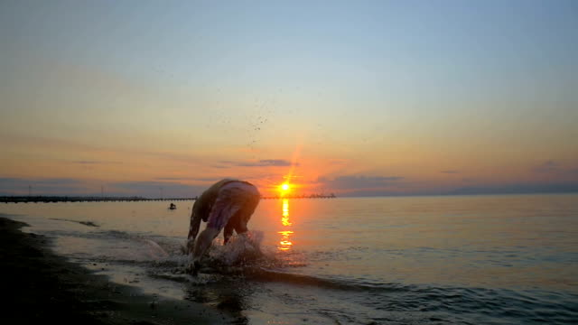 Athlete doing acrobatic tricks on the beach at sunset video