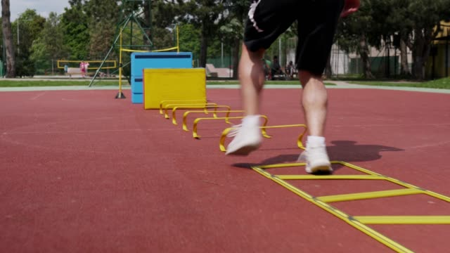 Athlete doing skipping on training ladder as part of outdoor obstacles course video