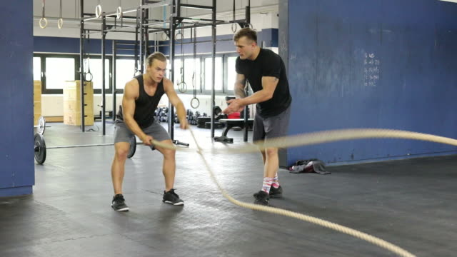 Athlete exercising with ropes in gym video