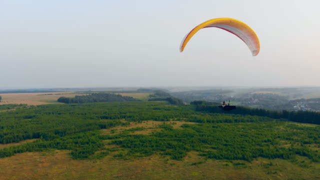 Athlete flies a glider in sky. Adventure, active extreme lifestyle concept.