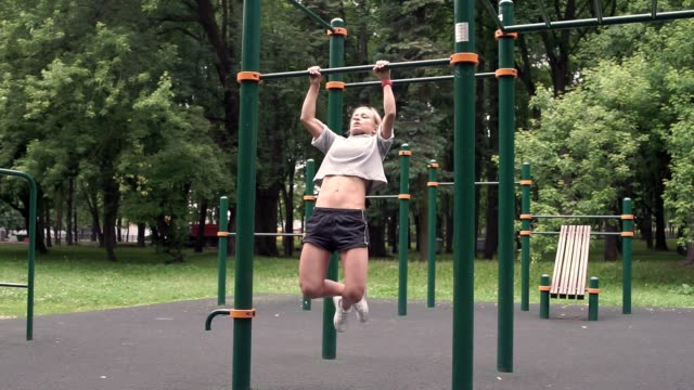 Athlete girl do pulling up on the bar on horizontal bar outdoor in a park Athlete girl do pulling up on the bar on horizontal bar outdoor in a park bodyweight training stock videos & royalty-free footage