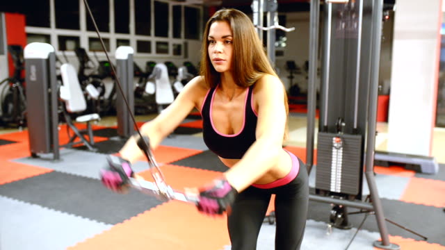 Athlete girl in sportswear working out and training her arms and shoulders gym video