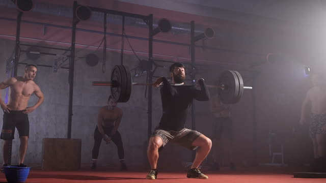 Athlete going to beat barbell snatch record at the gym with supporting team in slow motion video