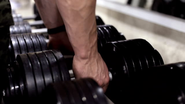 Athlete in the gym training with dumbbells - vídeo