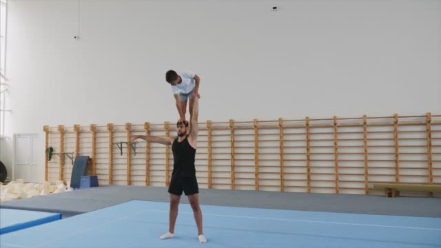 Athlete is making a handstand with one hand on the head of partner, steadicam.