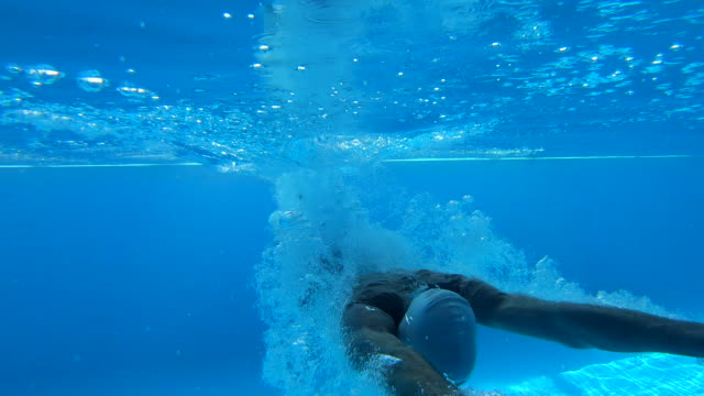 Athlete jumping in to a swimming pool Senior man, an athlete with sports equipment diving in to water in a swimming pool. retirement stock videos & royalty-free footage