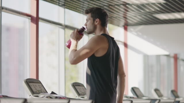 athlete man drinking water at cardio training on treadmill machine. - runner rehab gym video stock e b–roll