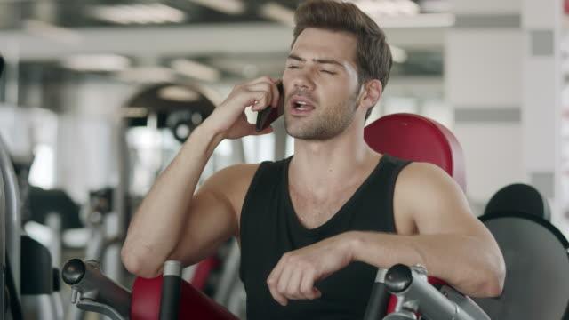 stockvideo's en b-roll-footage met atleet man praten smartphone na training over sport machine in fitness gym - call center
