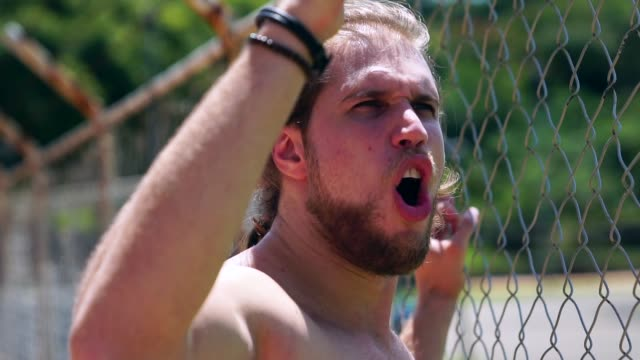 athlet mann gerade ein spiel auf der tribüne zaun - nackter oberkörper stock-videos und b-roll-filmmaterial
