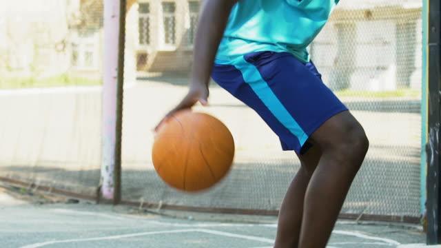 vídeos de stock e filmes b-roll de athlete playing basketball, dribbling ball skillfully to bypass opponent, sports - campeão desportivo
