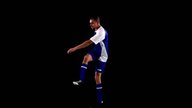Atleta practicando fútbol sobre fondo negro - vídeo