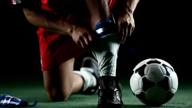 atleta preparazione a giocare a calcio. - annodare video stock e b–roll