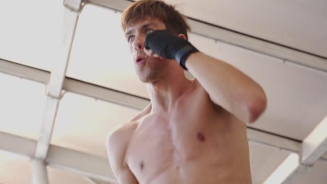 atleta pugile professionista in boxe punching allenamento riscaldarsi - sacco per il pugilato video stock e b–roll