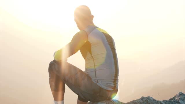 선수는 생각 하 고 산 위에 앉아 - mountain top 스톡 비디오 및 b-롤 화면